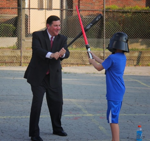 The Mayor battles Darth Vader with a wiffleball bat. Light sabers are no match for the wiffle stick.
